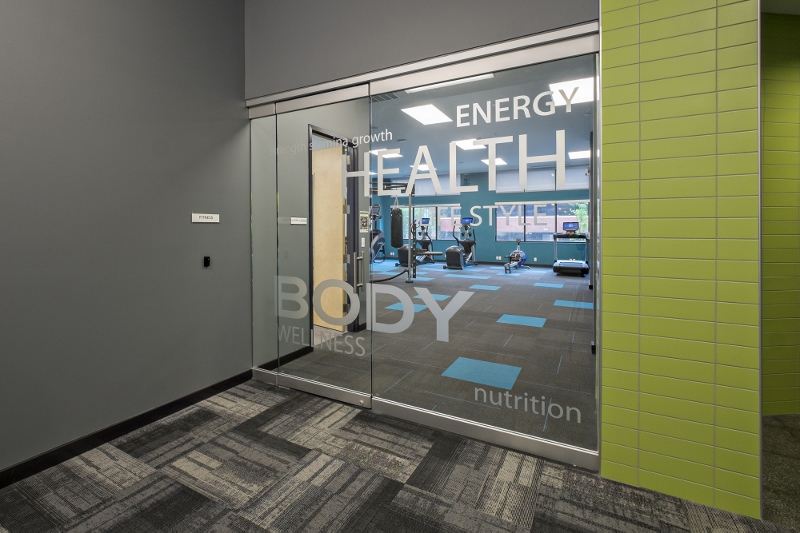 Glass-doored fitness center with workout equipment inside