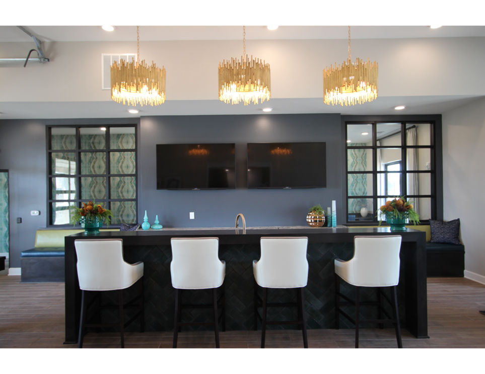 Clubhouse gathering space with bar seating and flatscreen TVs