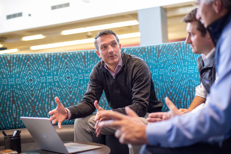 Three men meeting around a laptop