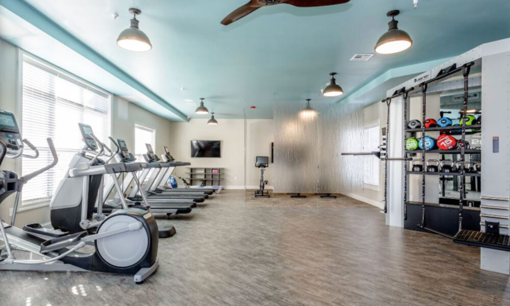 Spacious fitness center with a row of stationary bikes and rack of weights